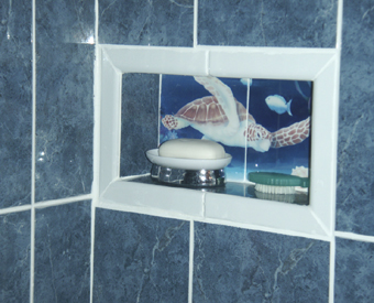 This small sea turtle tile  mural is the perfect back drop to a soap holder shelf in this unique bathroom. Love the idea and the look of the white trim used to surround the shelf.