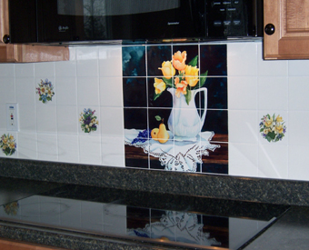 A tile mural of a white pitcher filled with yellow tulips is a great addition to this kitchen  backsplash tile project. Notice the flower accent tiles used throughout the whole area. Using accent tiles brings the whole look and theme  together. Awesome tile installation job!